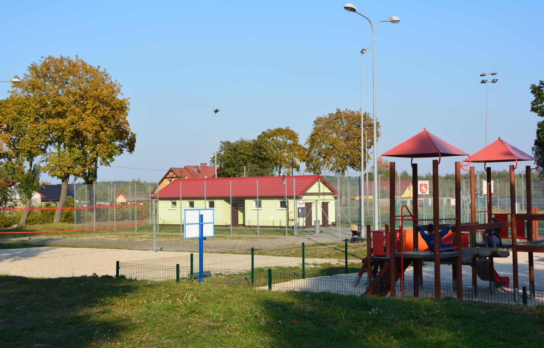 boisko, plac zabaw i budynek kryty czerwonym dachem