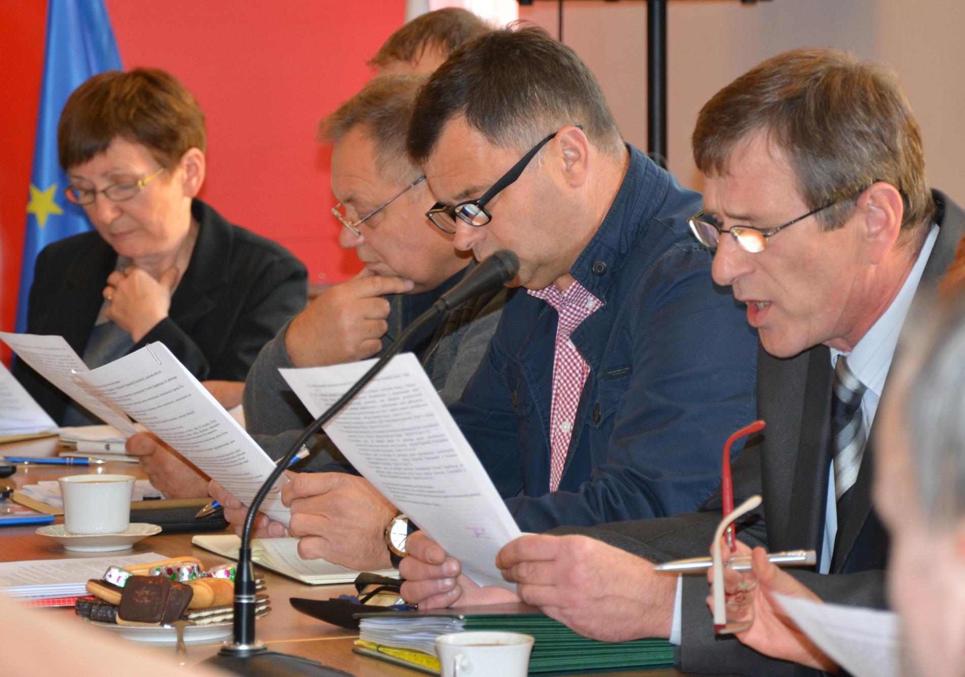 Osoby siedzą przy stole i czytaja dokumenty